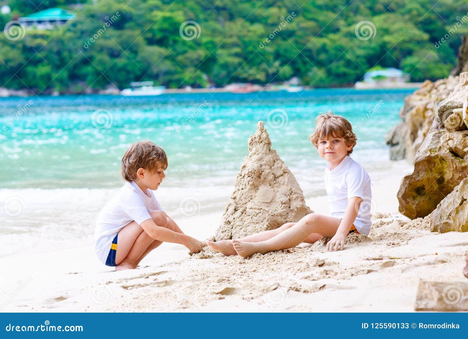 Deux garçons de petits enfants ayant l amusement avec construire un château de sable sur la plage tropicale des Seychelles Enfant