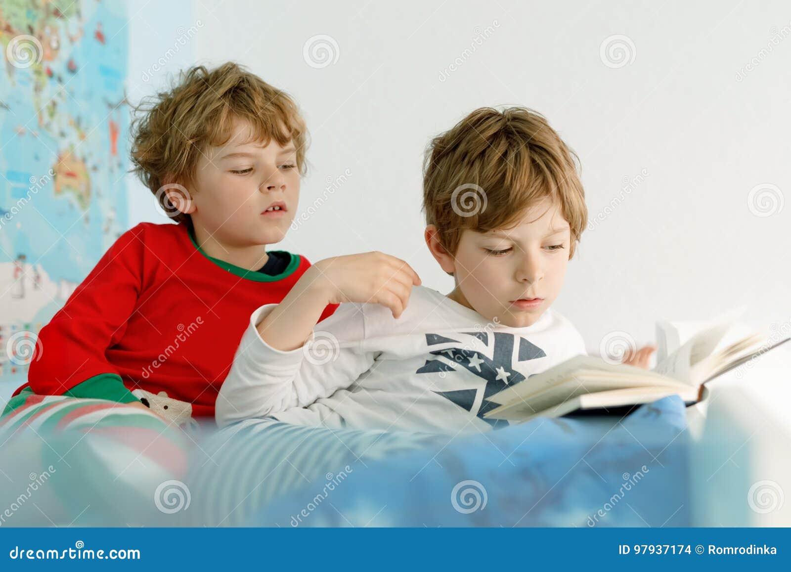 13514c1620a58 Deux garçons de petits enfants dans des pyjamas lisant un livre dans le lit