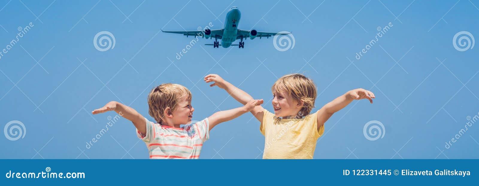 Deux garçons heureux sur la plage et un avion d atterrissage Voyageant avec la BANNIÈRE de concept d enfants, long format