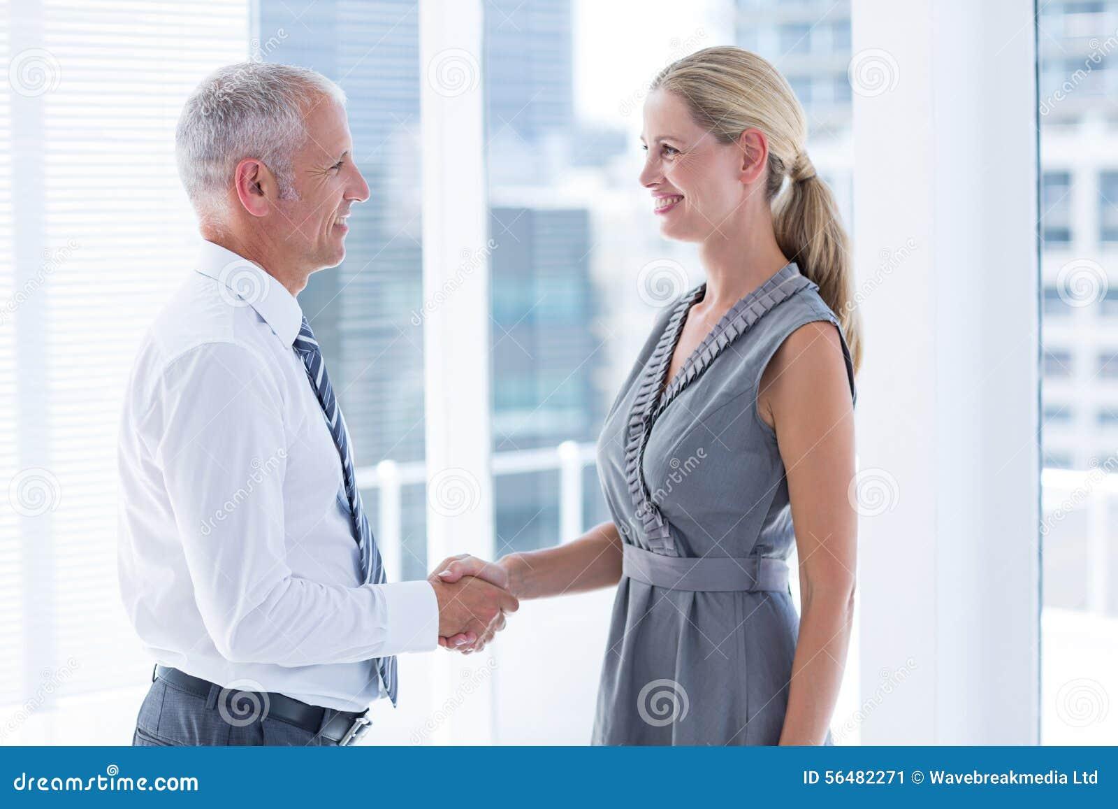 Deux gens d affaires de sourire se serrant la main
