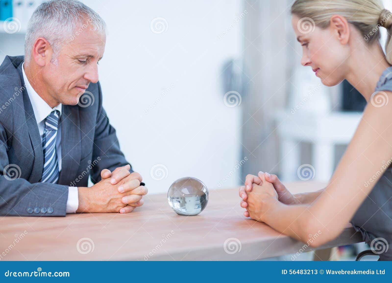 Deux gens d affaires pensant avec de la boule de cristal