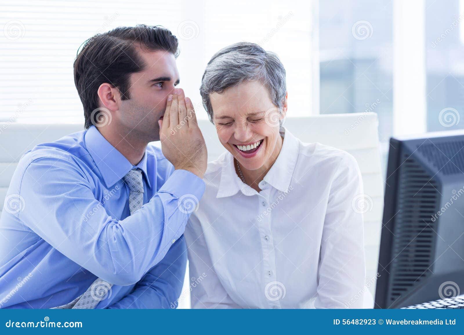 Deux gens d affaires regardant un papier tout en travaillant sur l ordinateur