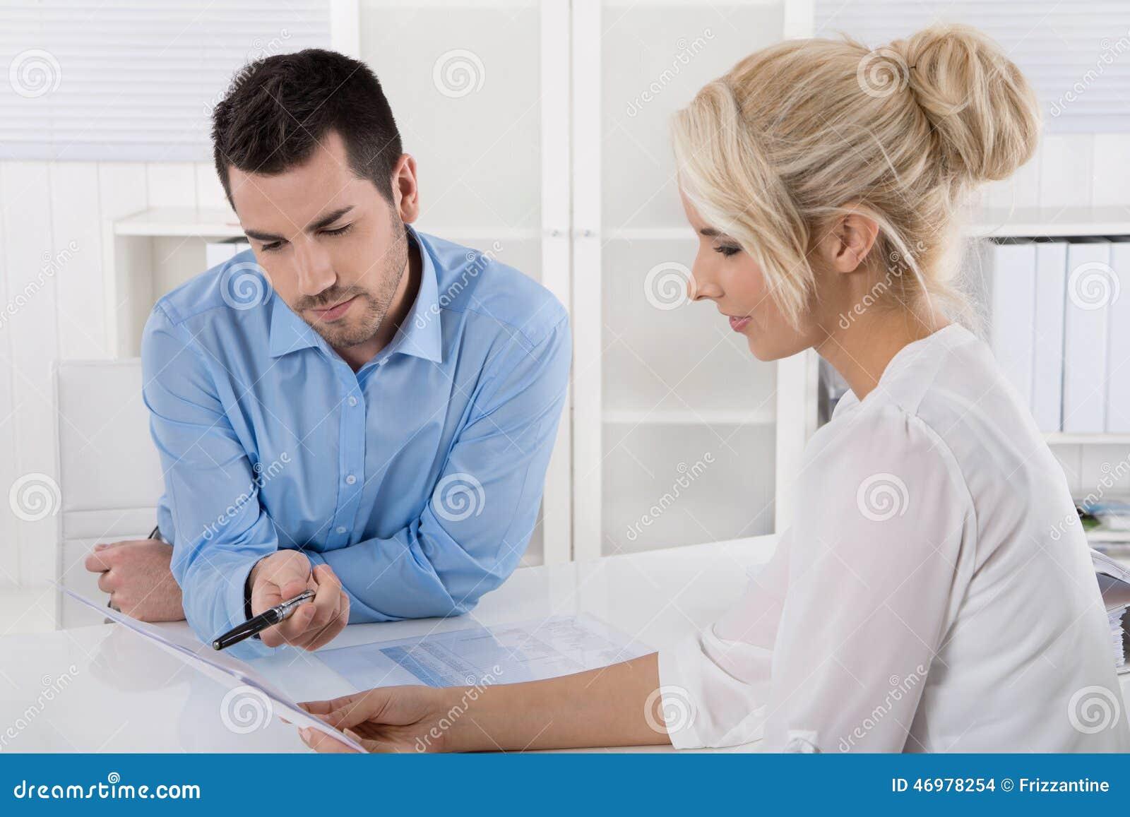 Deux gens d affaires s asseyant dans le bureau fonctionnant dans une équipe regardent