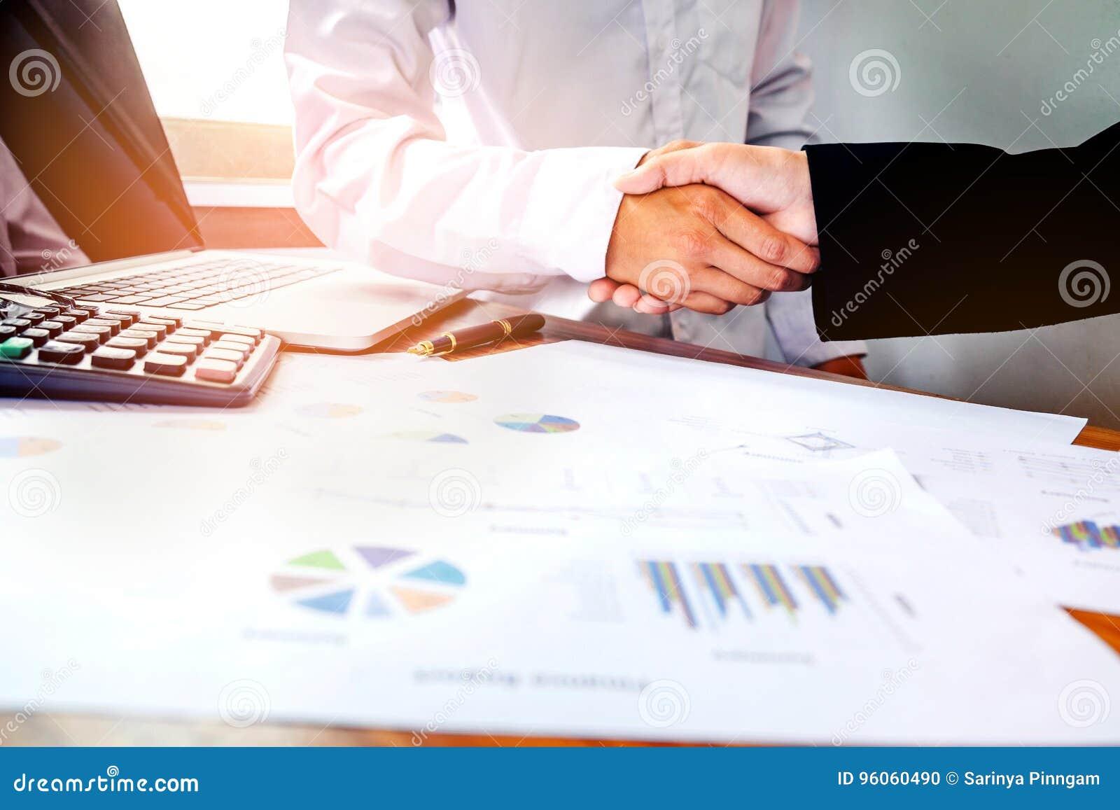 Deux gens d affaires se serrant la main tout en se reposant au p fonctionnant