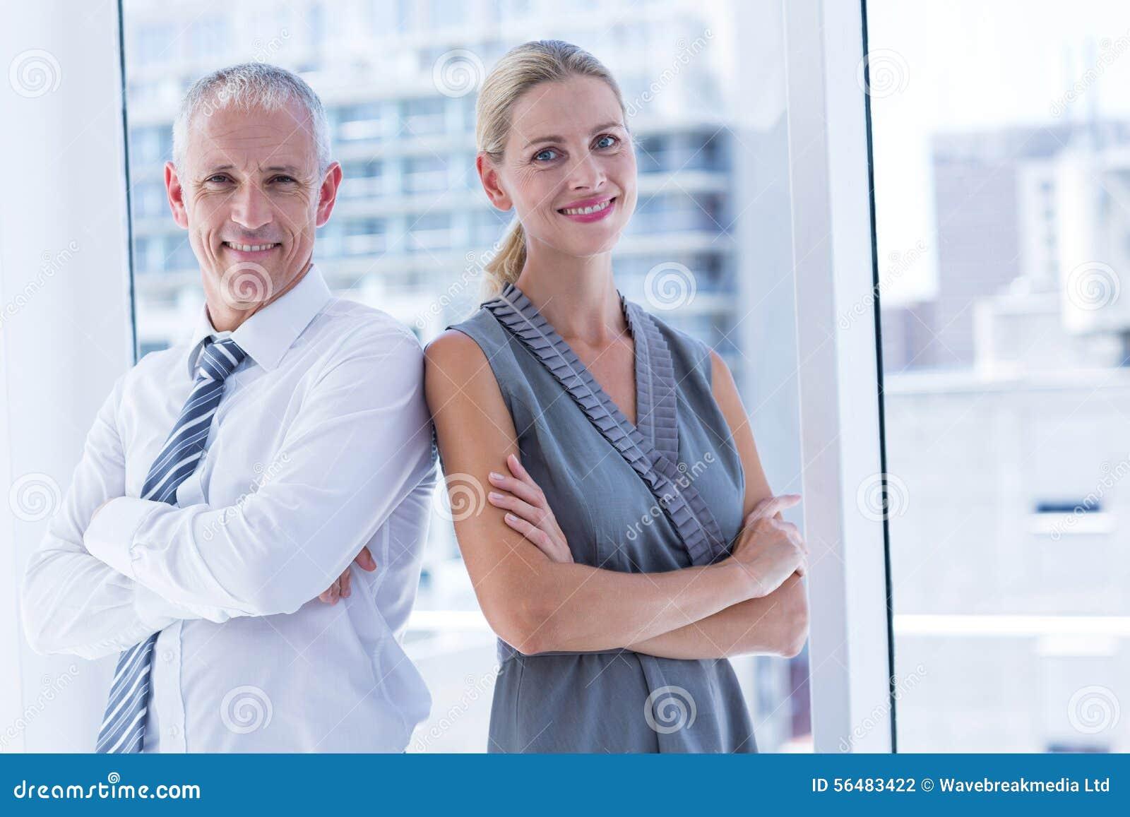 Deux gens d affaires souriant à l appareil-photo dans le bureau