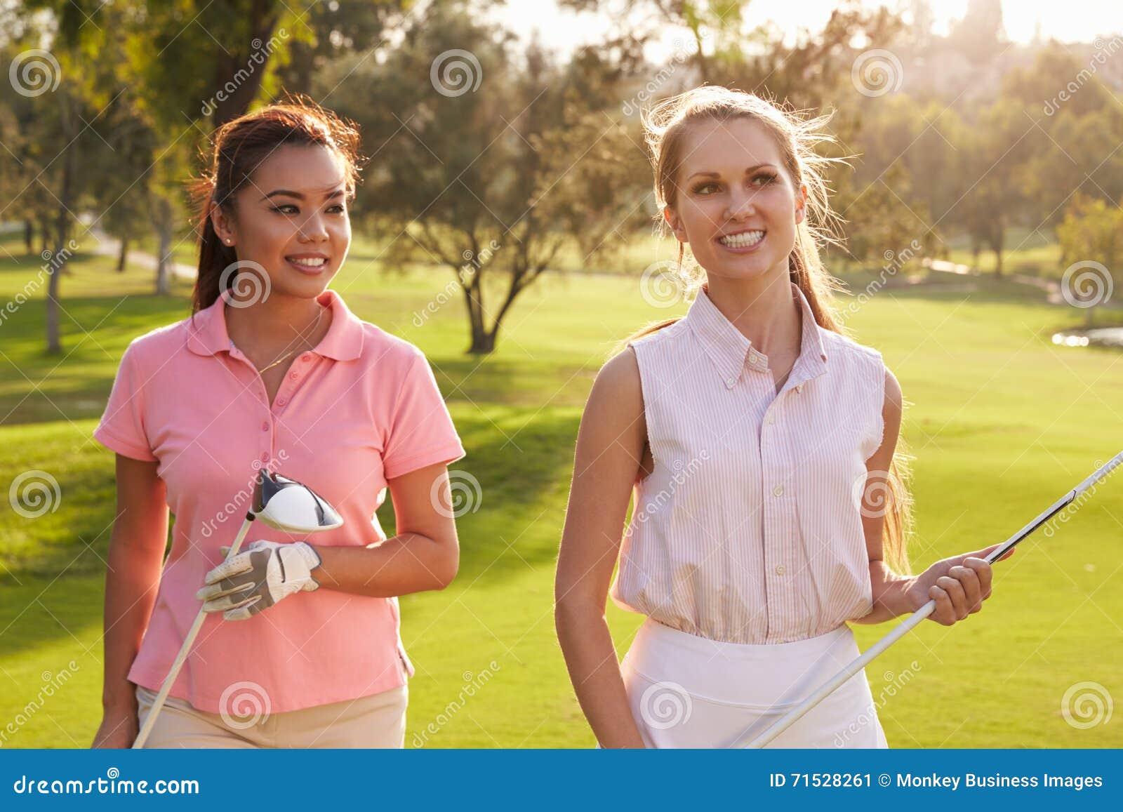 Deux golfeurs féminins marchant le long des clubs de transport de fairway