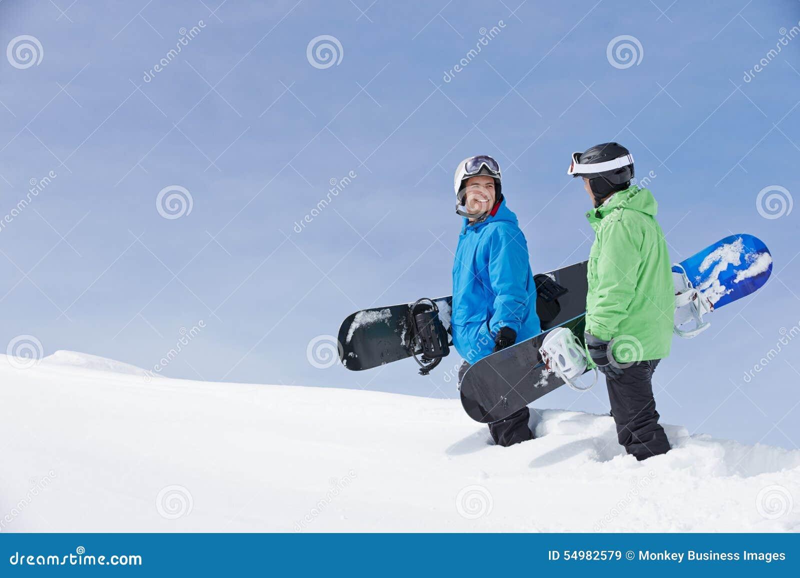 Deux hommes avec des surfs des neiges sur Ski Holiday In Mountains