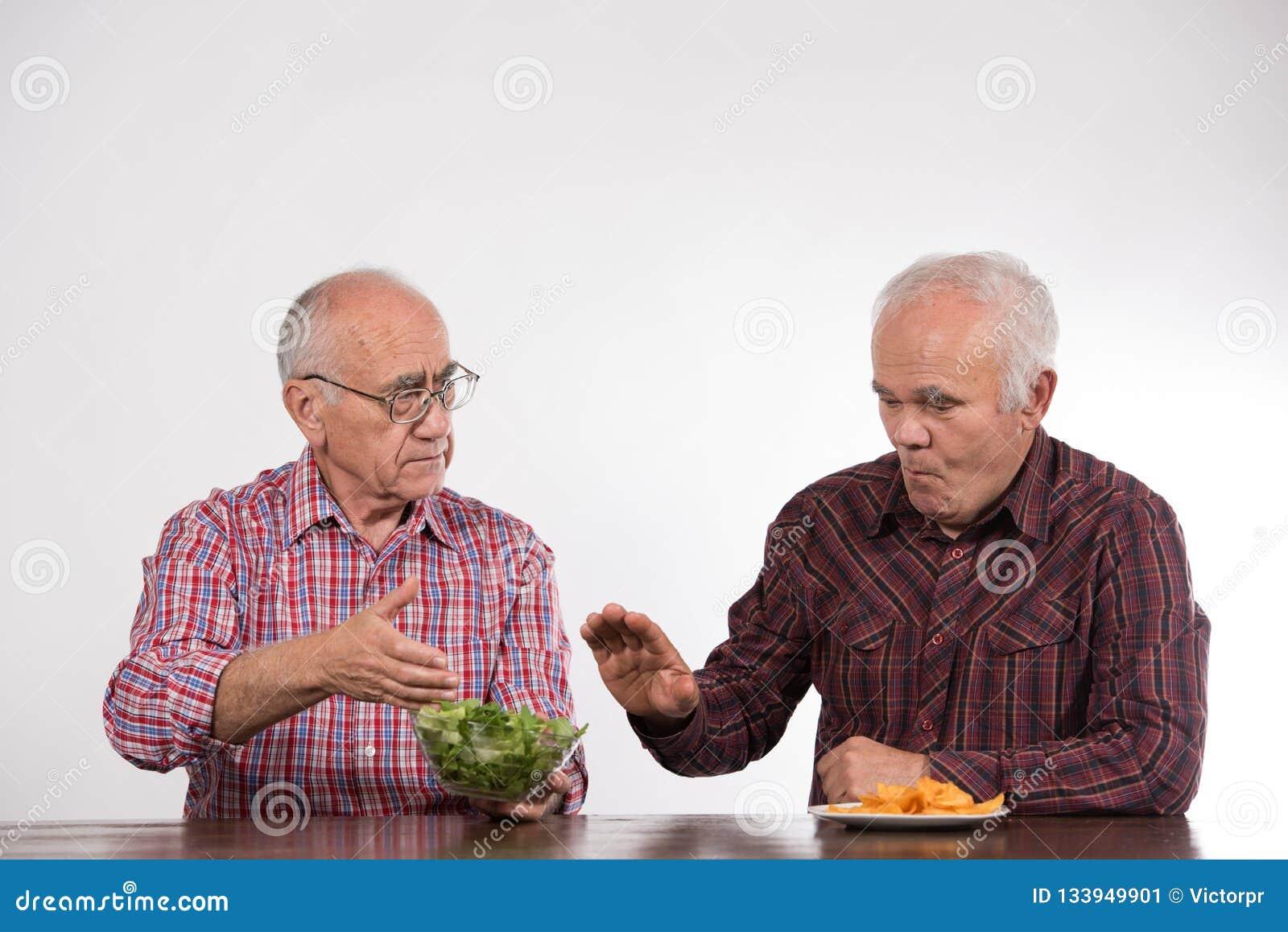 Deux hommes avec sain et la nourriture industrielle