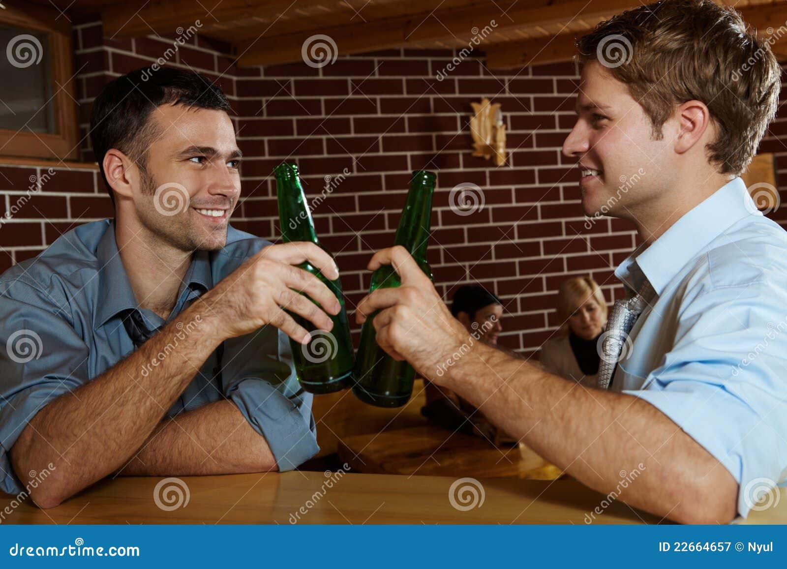 Deux hommes buvant de la bière dans le bar