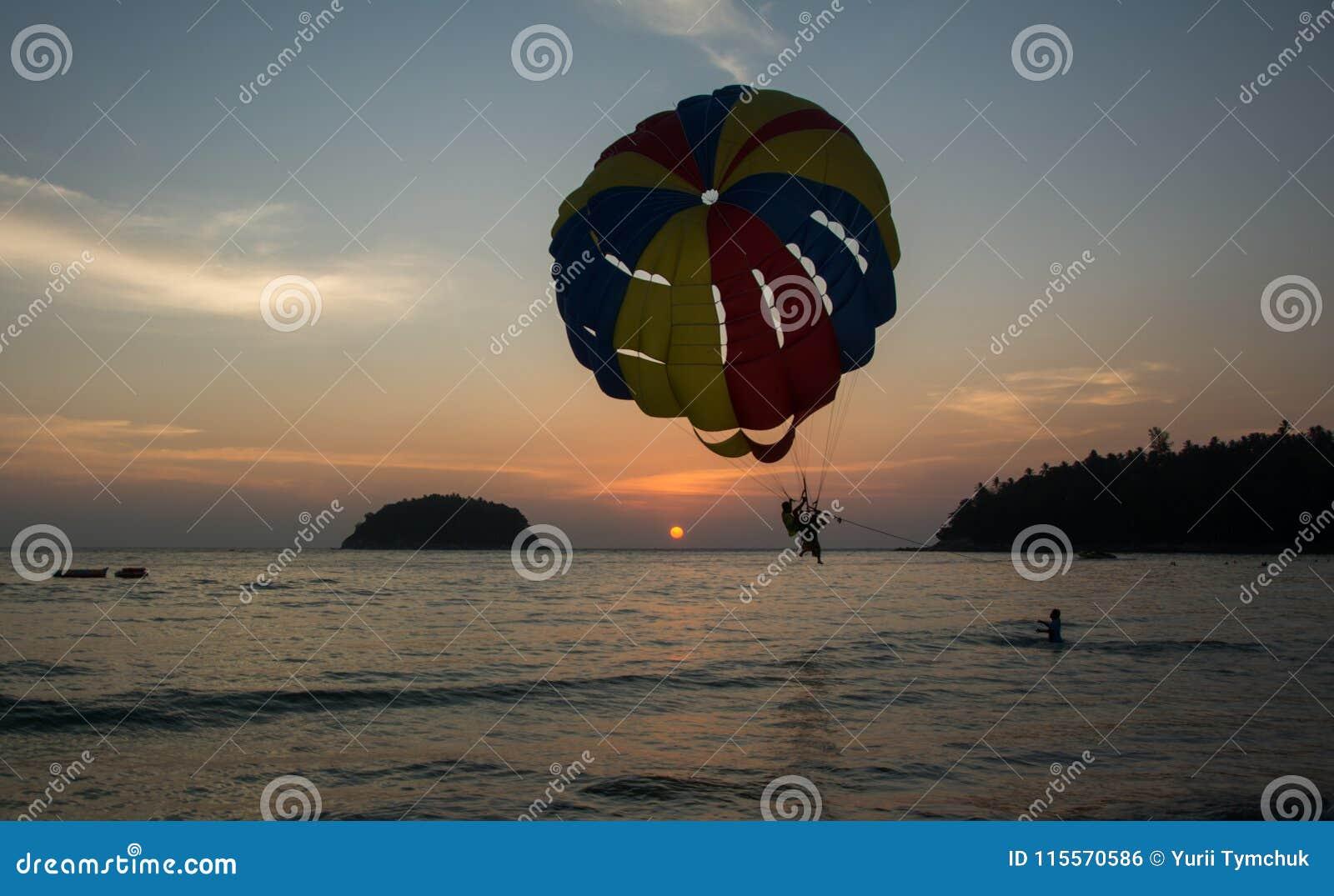 Deux hommes débarquant sur paraseiling sur le coucher du soleil, sports extrêmes