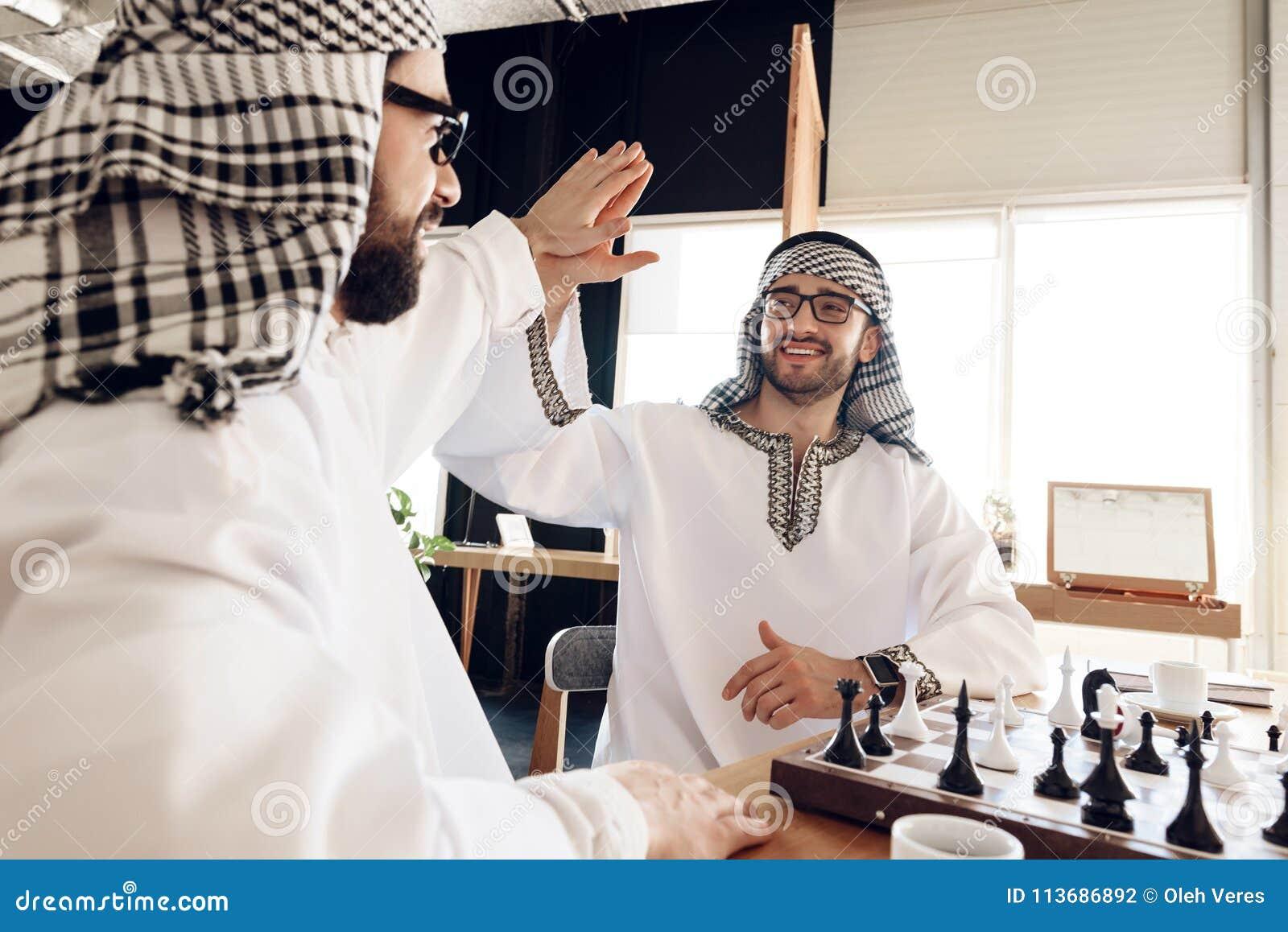 Deux hommes d affaires arabes hauts cinq derrière l échiquier à la chambre d hôtel