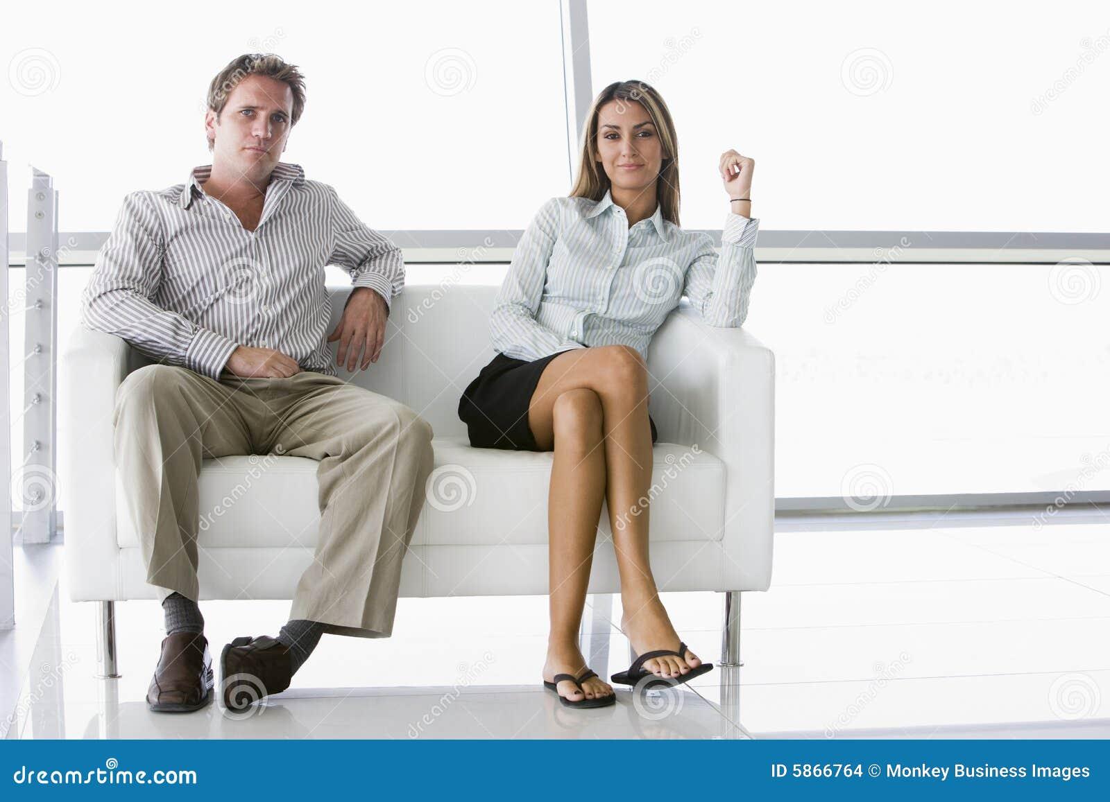 Deux hommes d affaires s asseyant dans le bureau font pression en faveur du sourire
