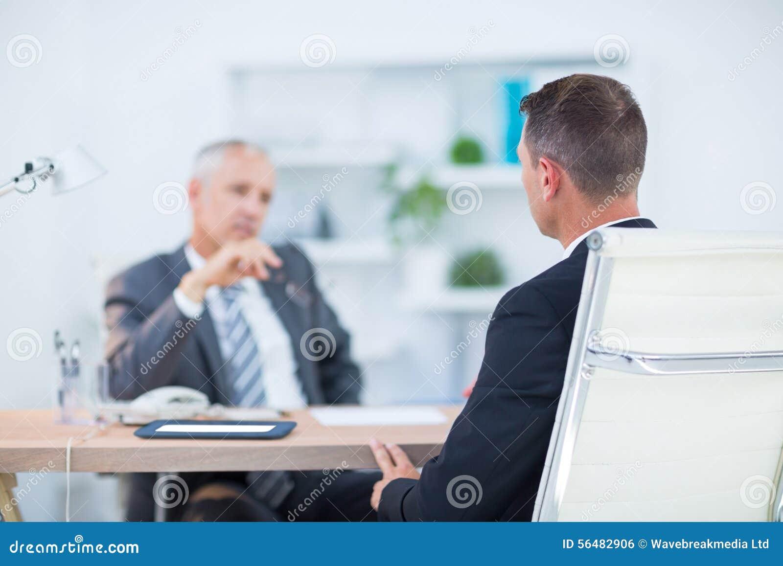 Deux hommes d affaires s asseyant et parlant