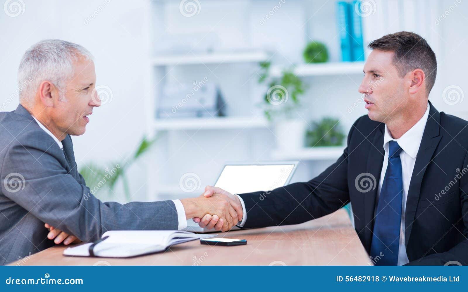 Deux hommes d affaires se serrant la main et le travail
