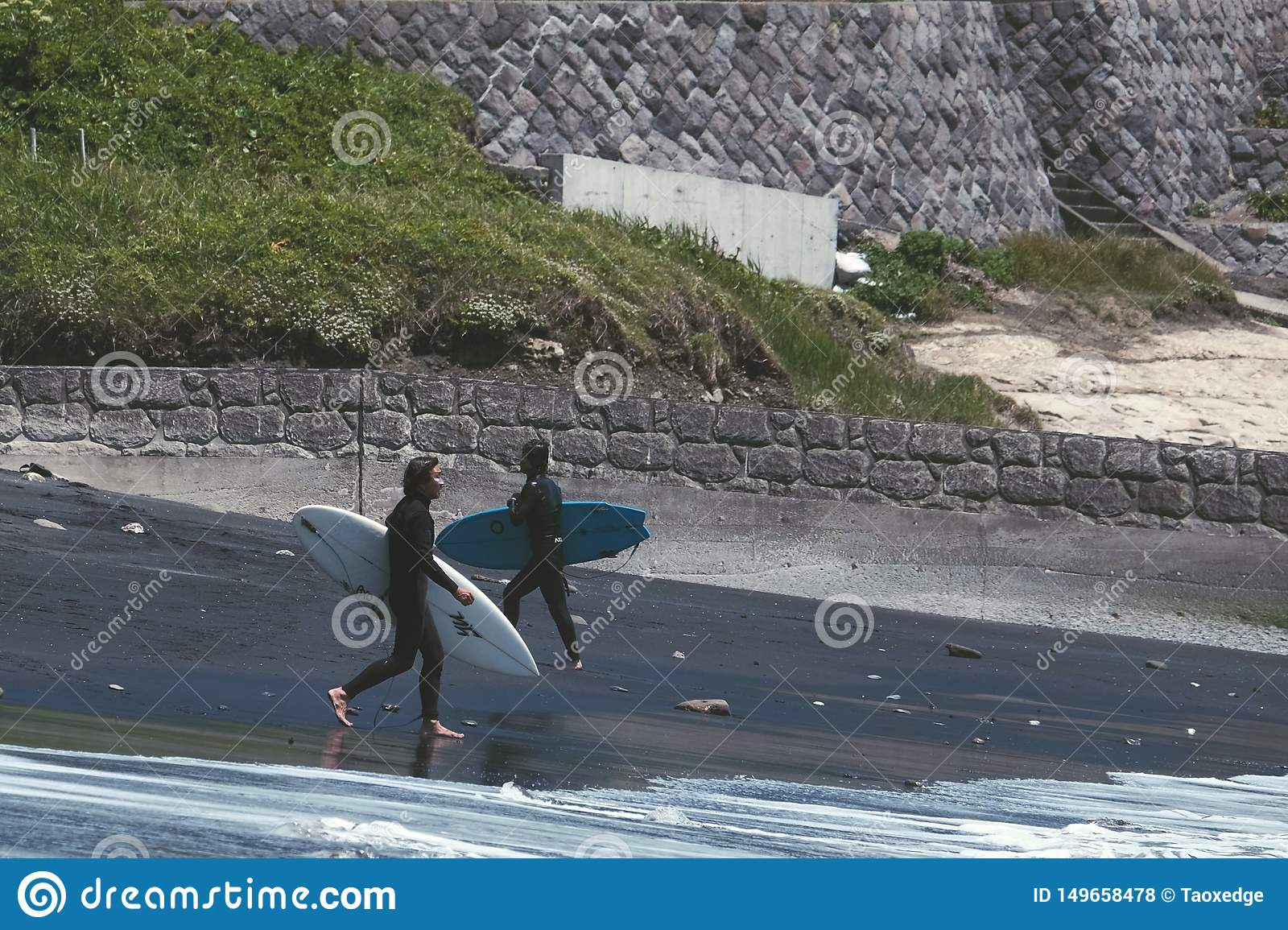 Deux hommes marchant sur une plage noire pour surfer