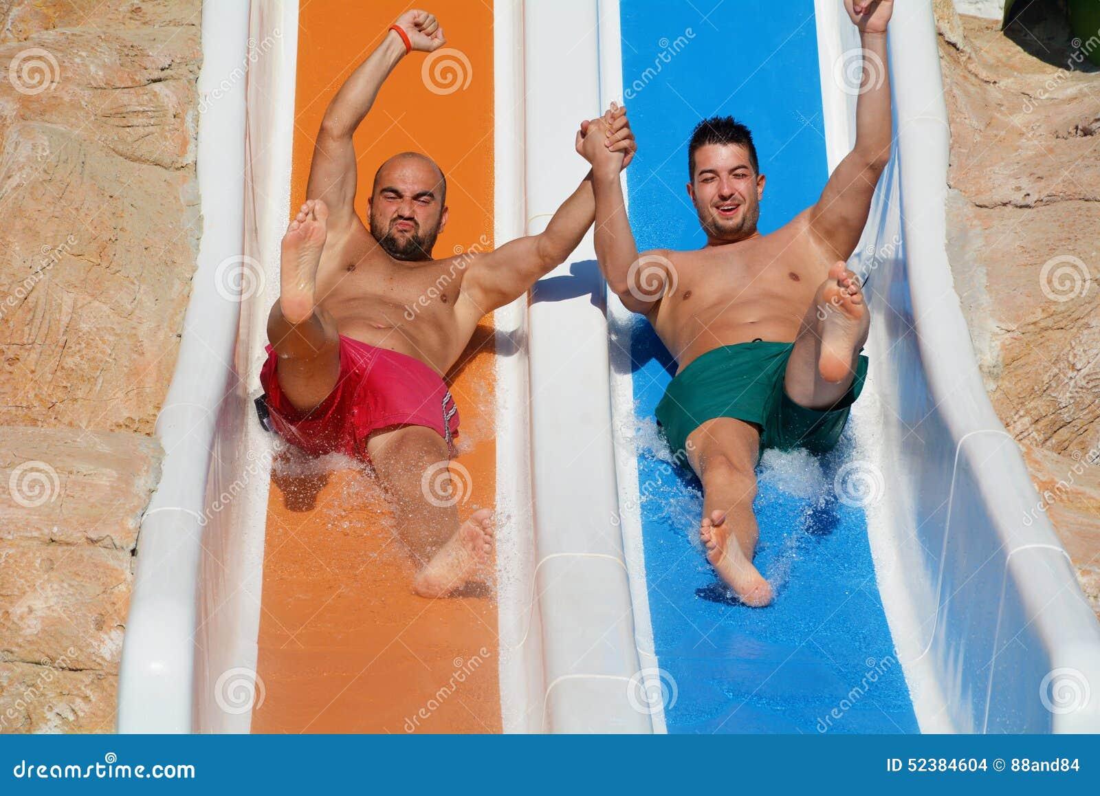 Deux hommes montant en bas des glissière-amis d une eau appréciant un tube de l eau montent