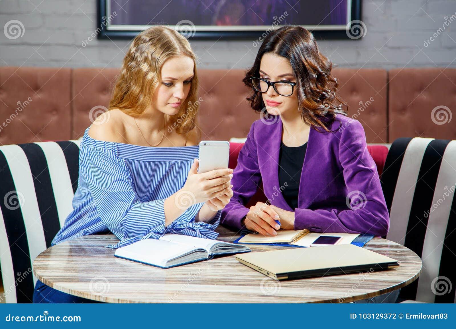 Deux indépendants discutent de nouveaux projets tout en se reposant dans un café avec des appareils électroniques