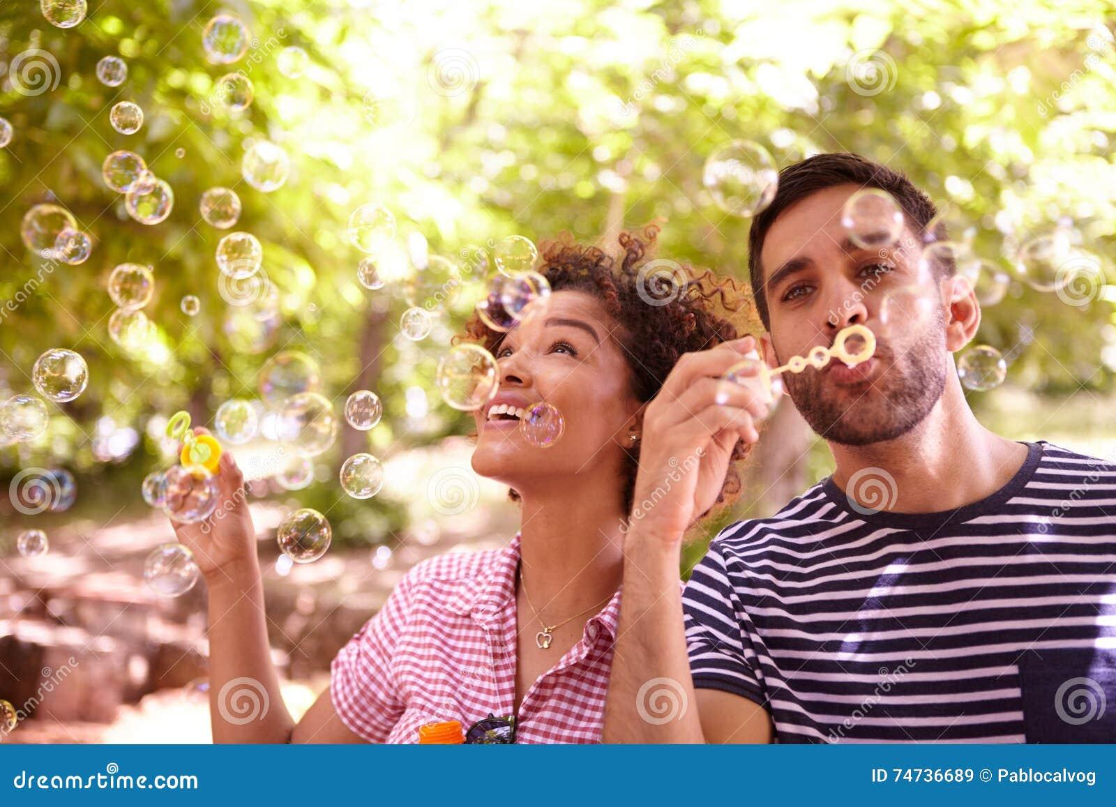 Deux jeunes amis heureux soufflant des bulles