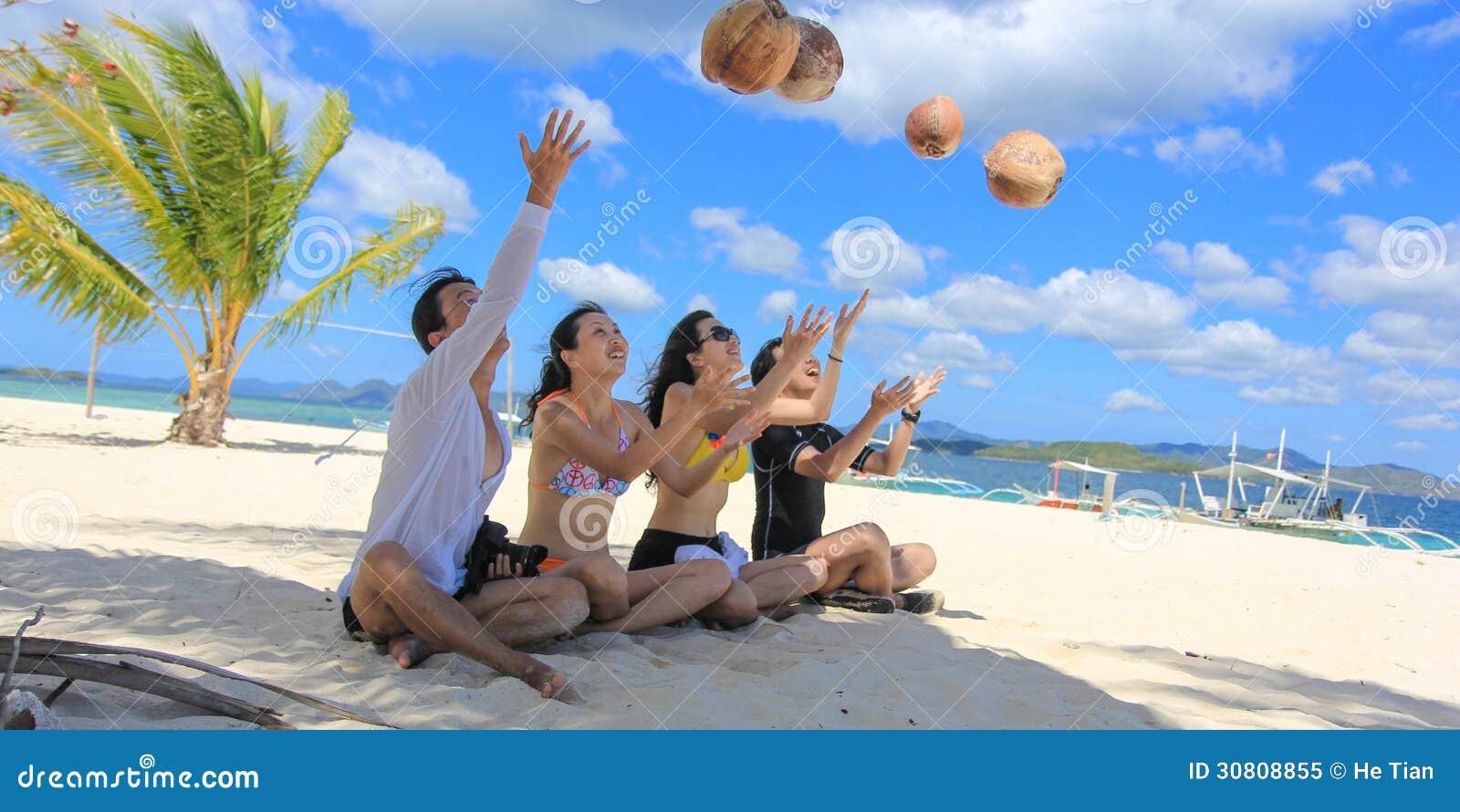 Deux jeunes couples heureux ayant l amusement sur la plage blanche tropicale