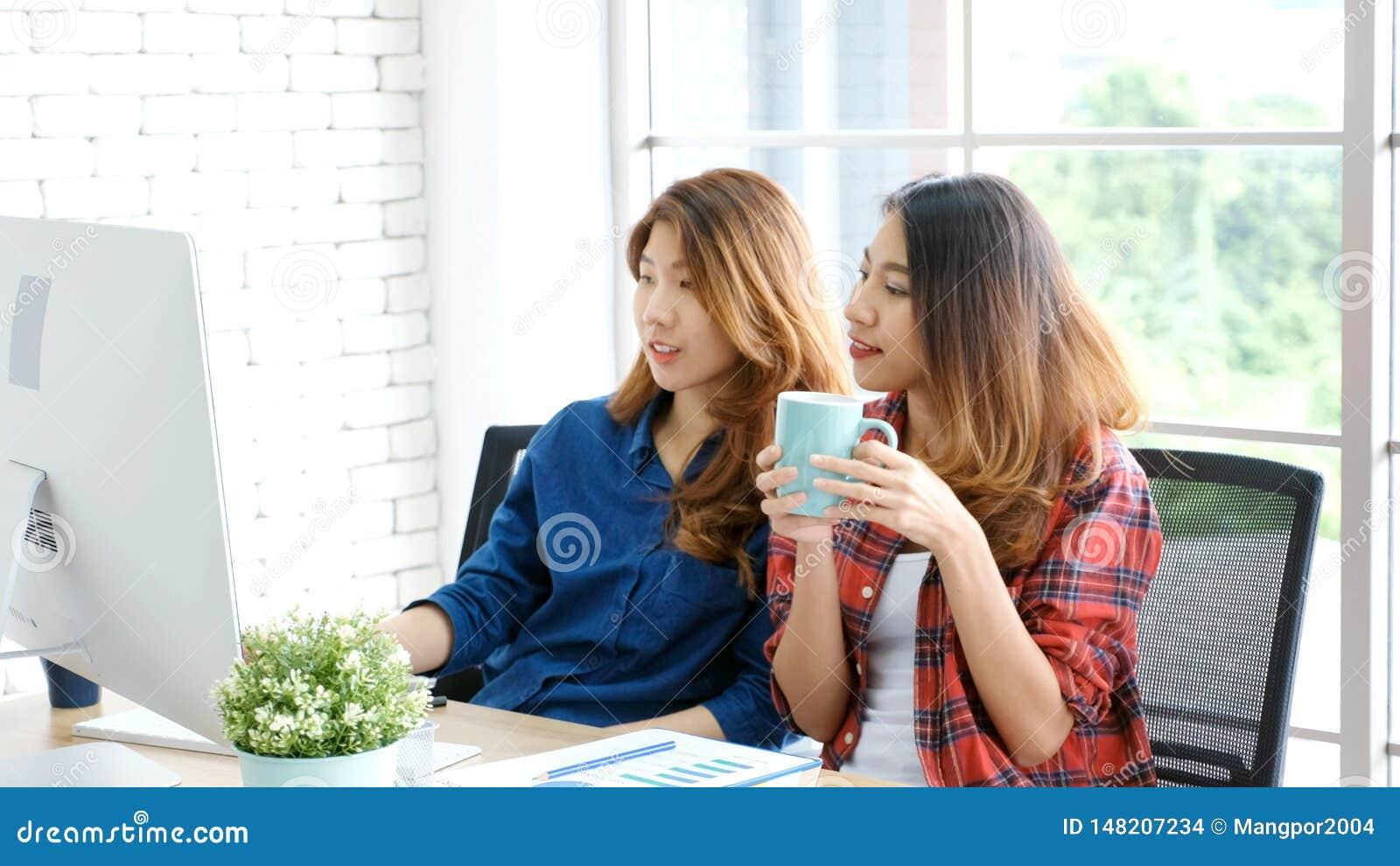 Deux jeunes femmes asiatiques travaillant avec le bureau d ordinateur ? la maison avec ?motion heureuse, fonctionnant ? la maison