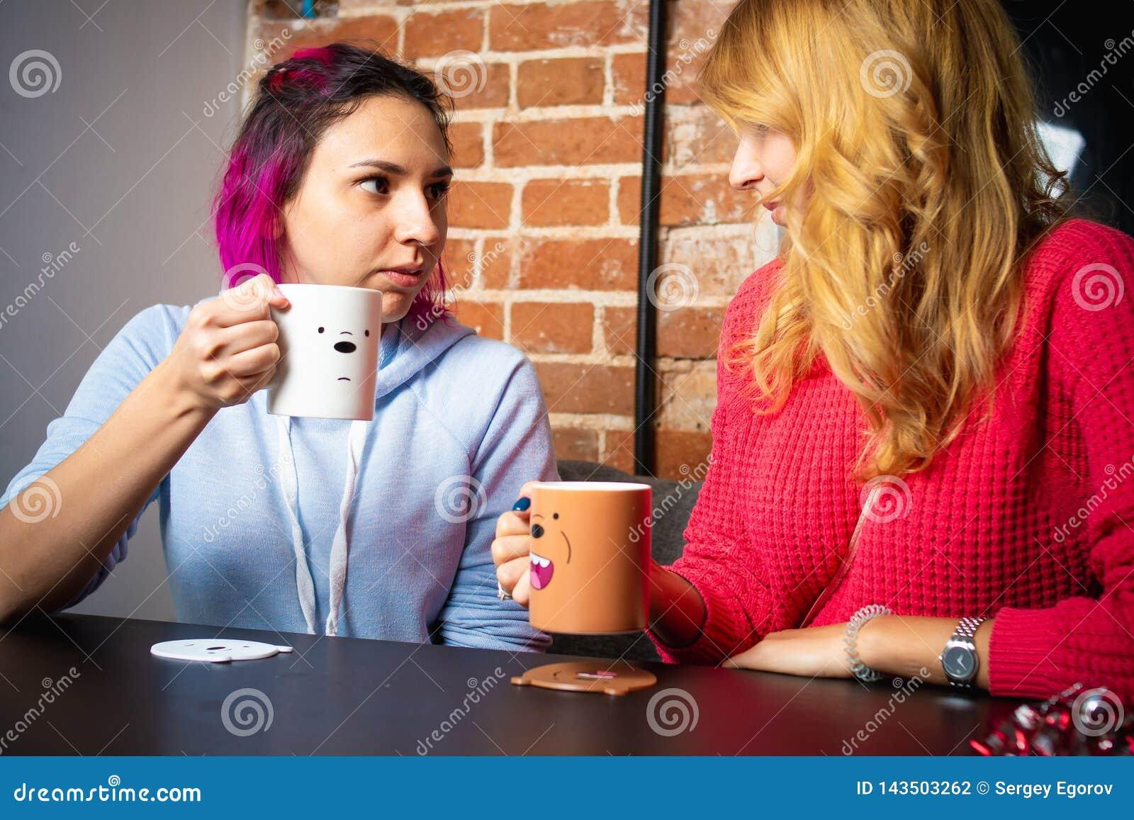 Deux jeunes femmes avec les tasses de parler de thé et de café