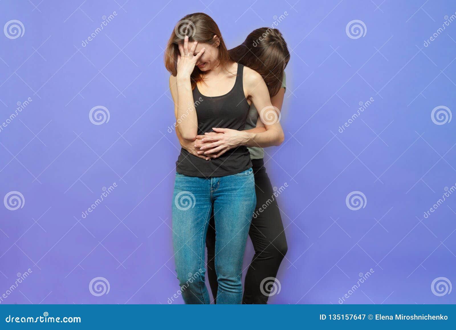 Deux jeunes femmes caucasiennes avec le support de cheveux foncés embrassant, une sans compter qu un autre avec la paume de visag
