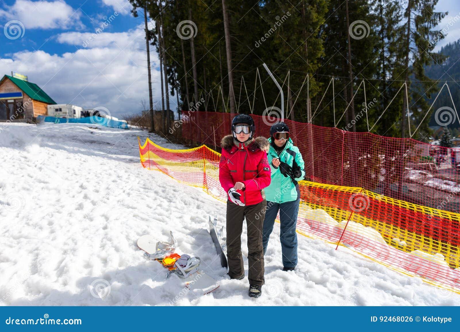 dc98e069e3 Deux jeunes femmes dans des costumes de ski, avec des casques et des lunettes  de ski se tenant près de la barrière dans une ski-station de vacances dans  la ...