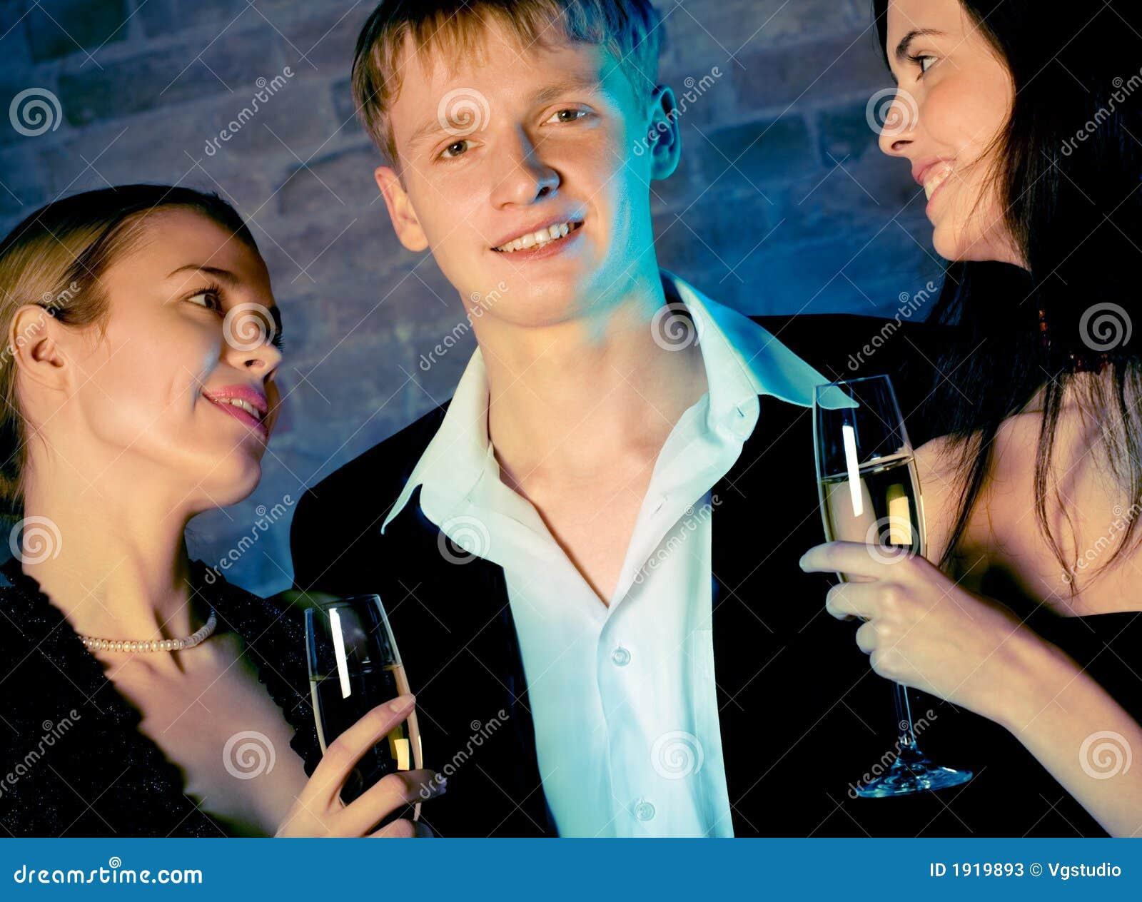 Deux jeunes femmes doux attirants et homme avec des glaces de champagne