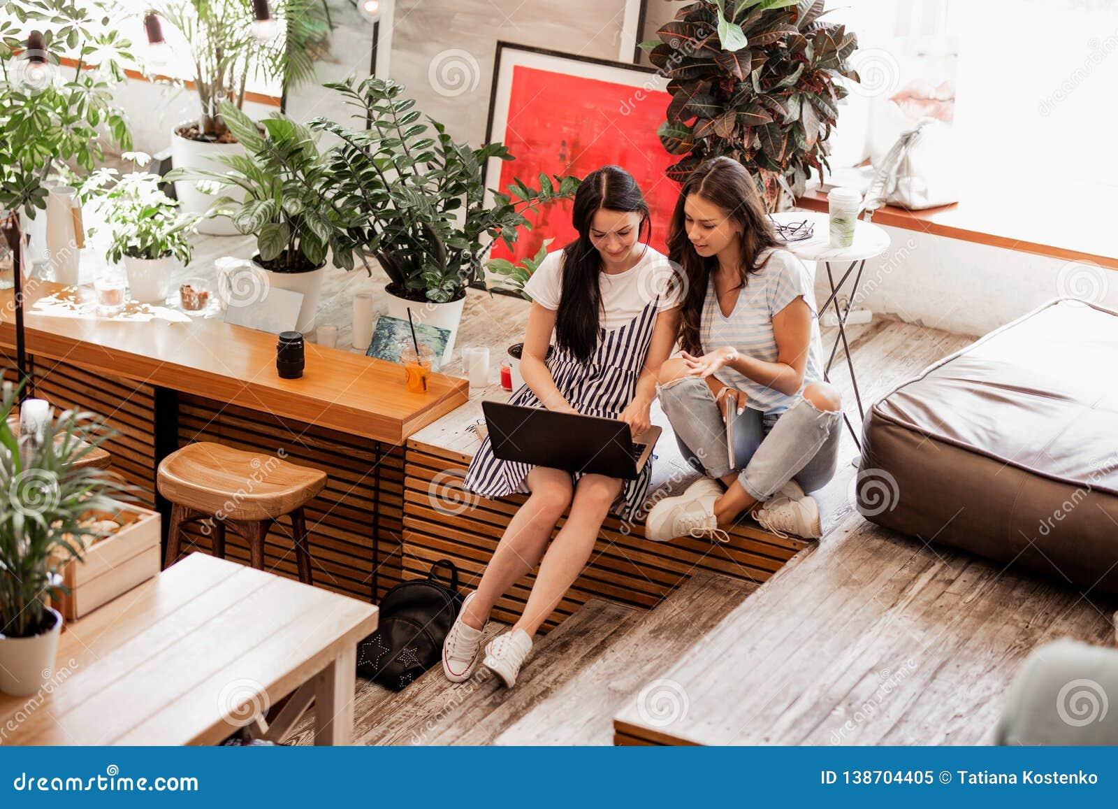 Deux jeunes filles de sourire avec de longs cheveux foncés, équipement occasionnel de port, s asseyent l un à côté de l autre et