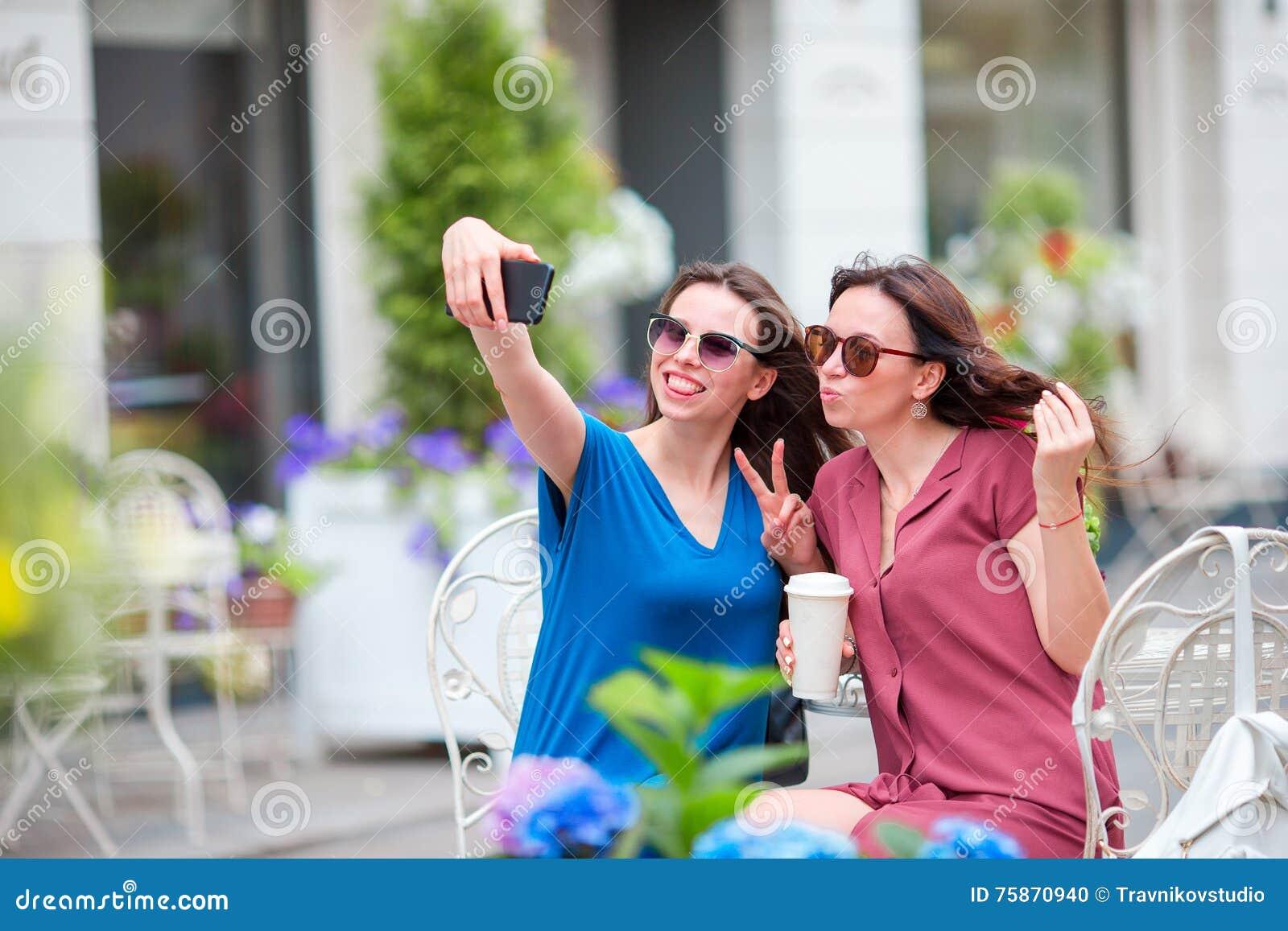 Deux jeunes filles prenant le selfie avec le téléphone intelligent au café d extérieur Deux femmes après l achat avec des sacs se