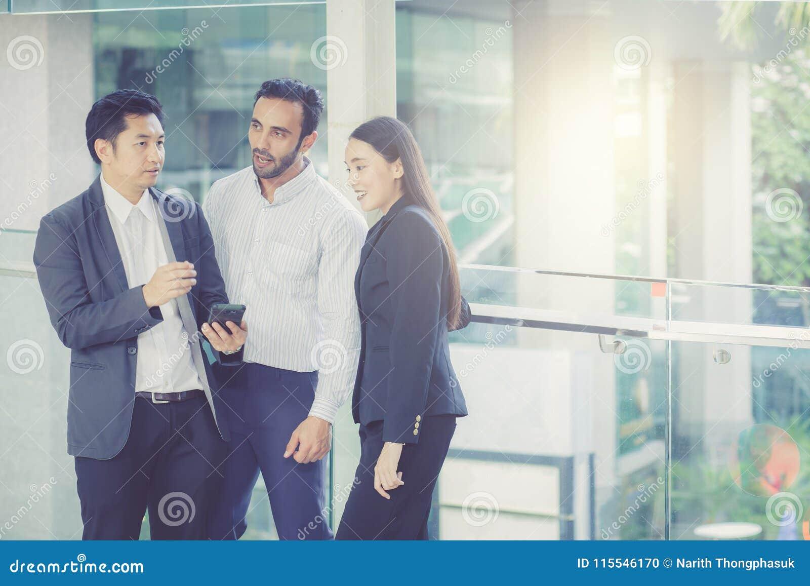 Deux jeunes hommes d affaires beaux et dame dans les costumes classiques tiennent des tasses de café, de parler et de sourire