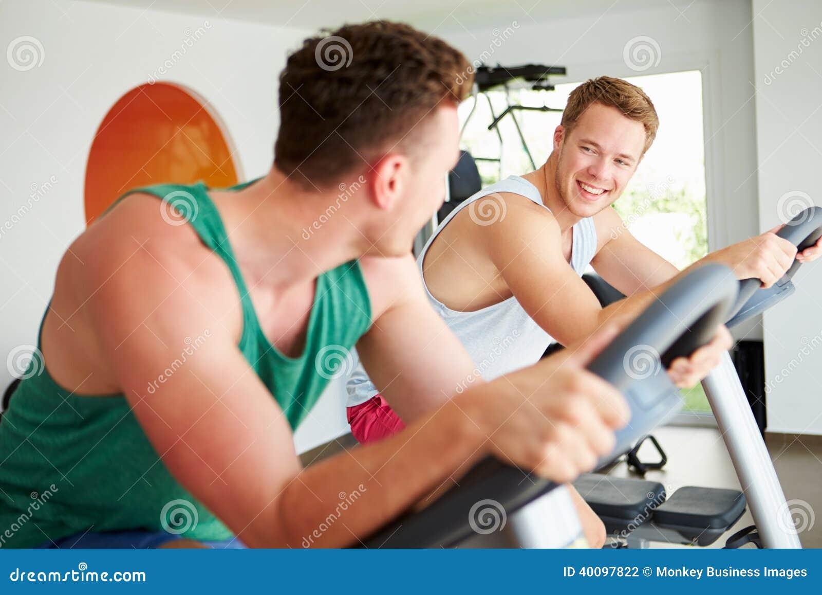 Deux jeunes hommes s exerçant dans le gymnase sur les machines de recyclage ensemble