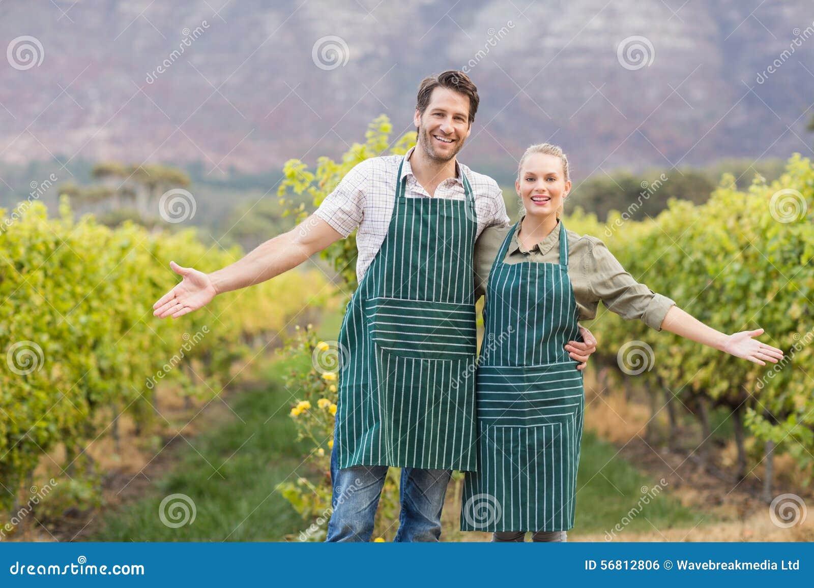 Deux jeunes négociants en vins heureux montrant leurs champs