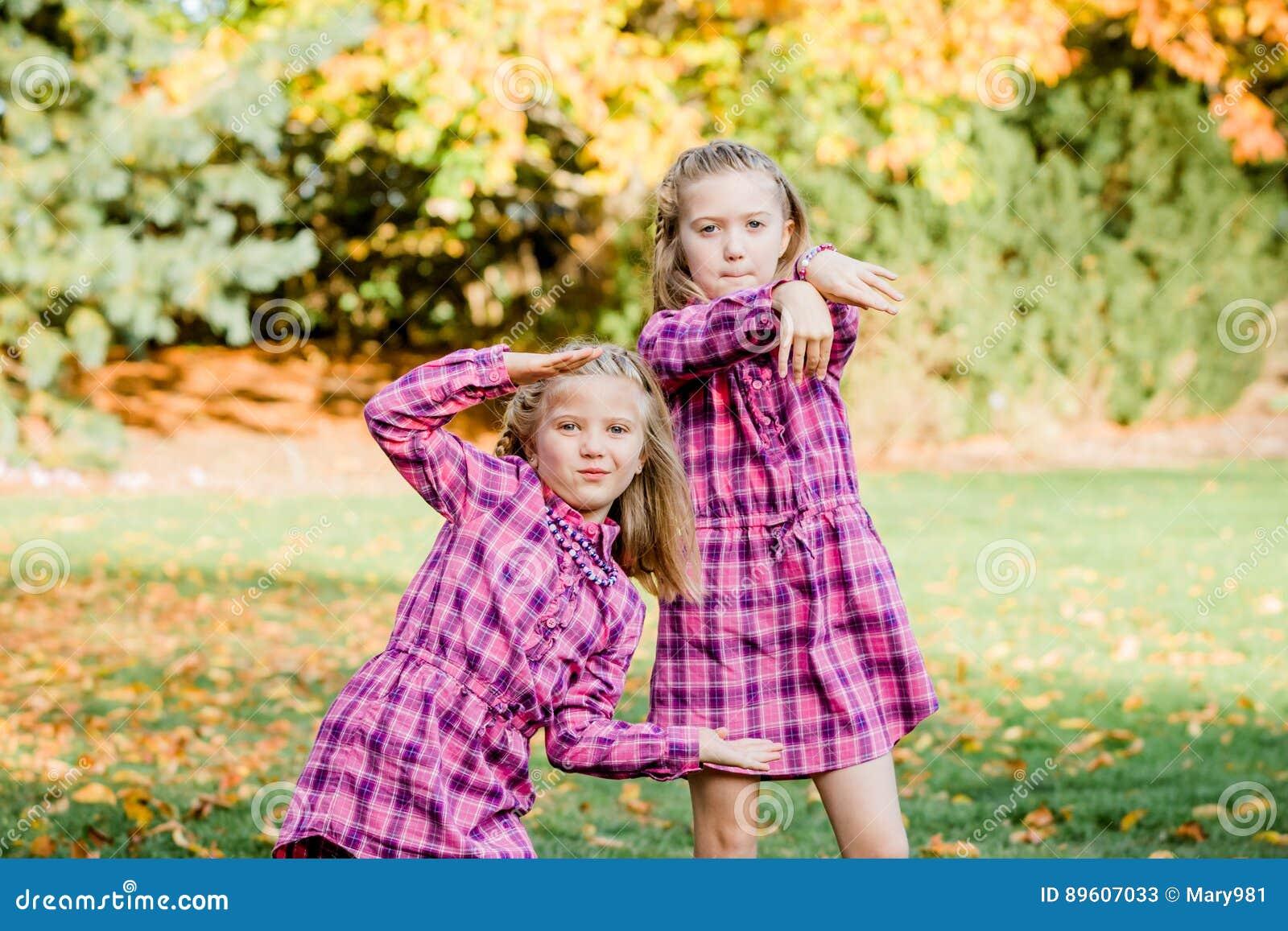 Deux jeunes soeurs caucasiennes frappent une pose en assortissant les robes roses de flanelle