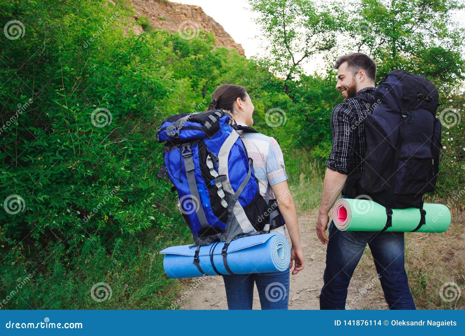 Deux jeunes touristes avec des sacs à dos Les amis heureux à l arrière-plan d herbe et de ciel bleu, détendent le temps en vacanc
