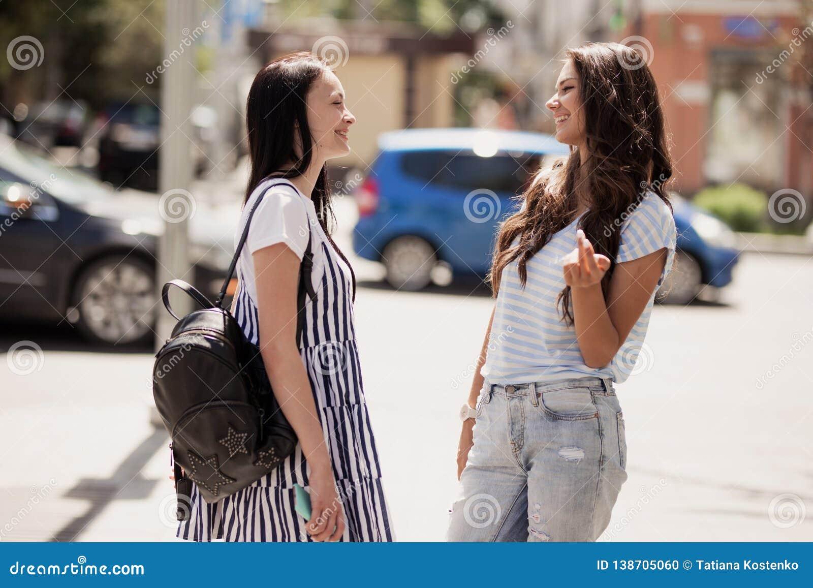 Deux jolies filles minces jeunes, équipement occasionnel de port, support à la rue et causerie