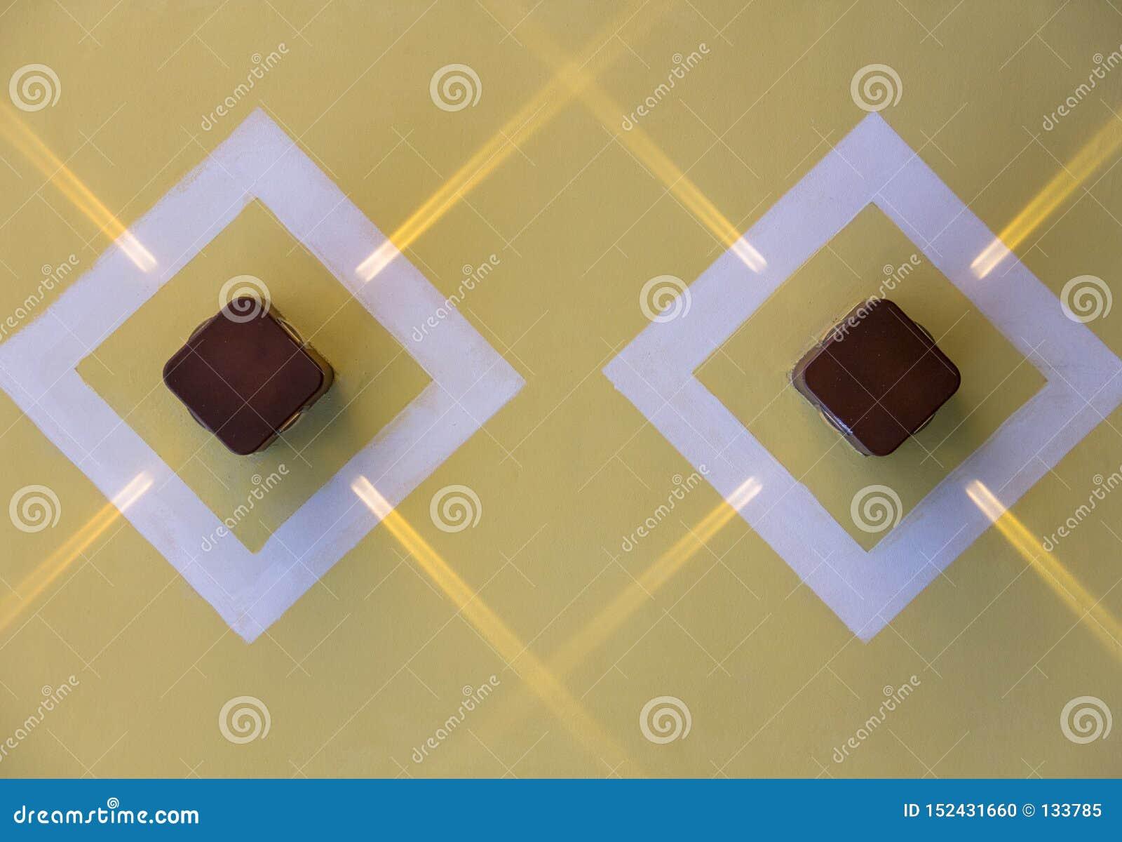 Deux lampes brunes carrées avec des rayons de lumière sur un mur jaune dans les losanges blancs Texture de surface approximative
