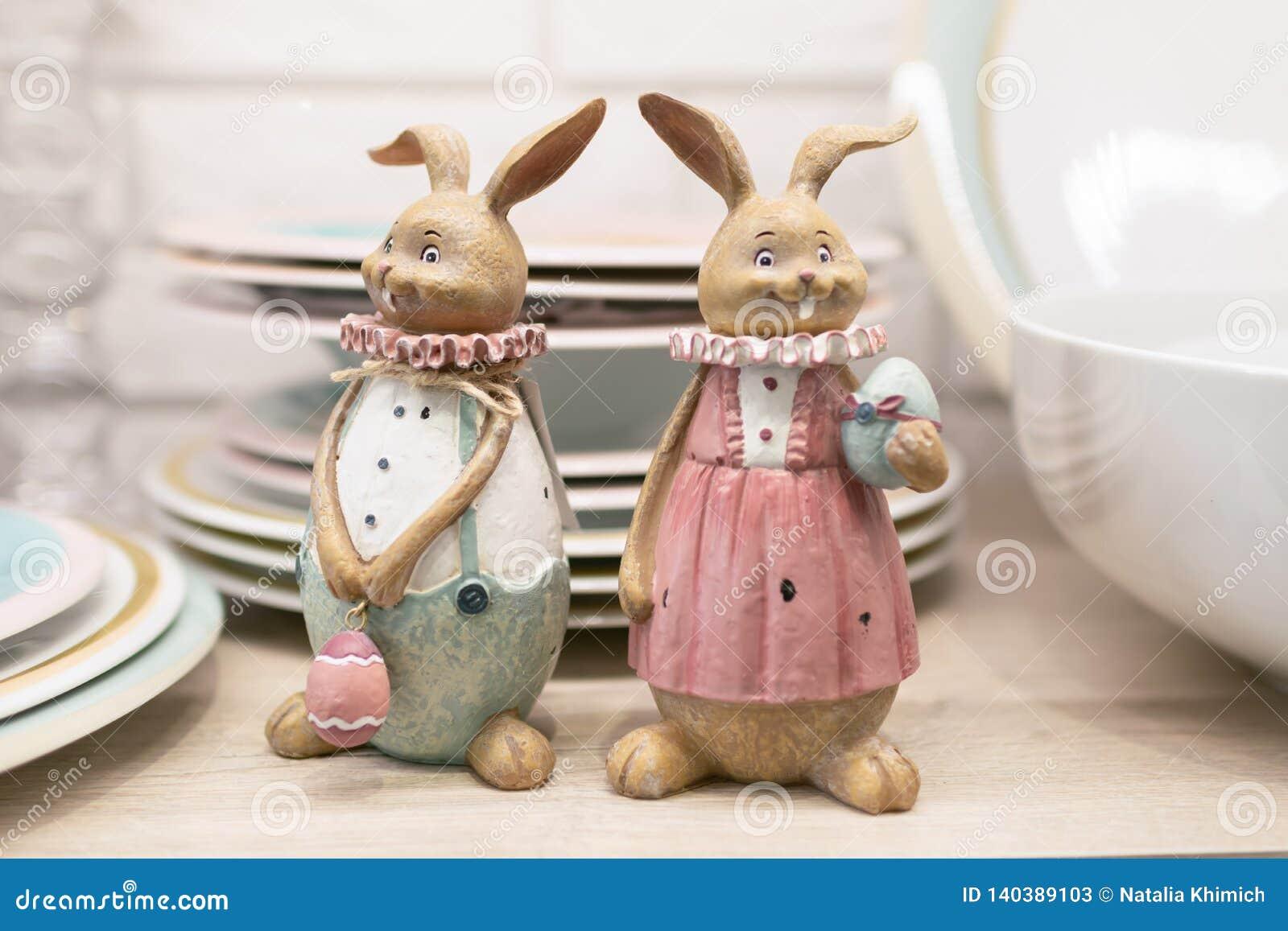 Deux lièvres de poterie de Pâques sur une étagère de table de cuisine Figurines en céramique pour servir la table de fête Foyer s