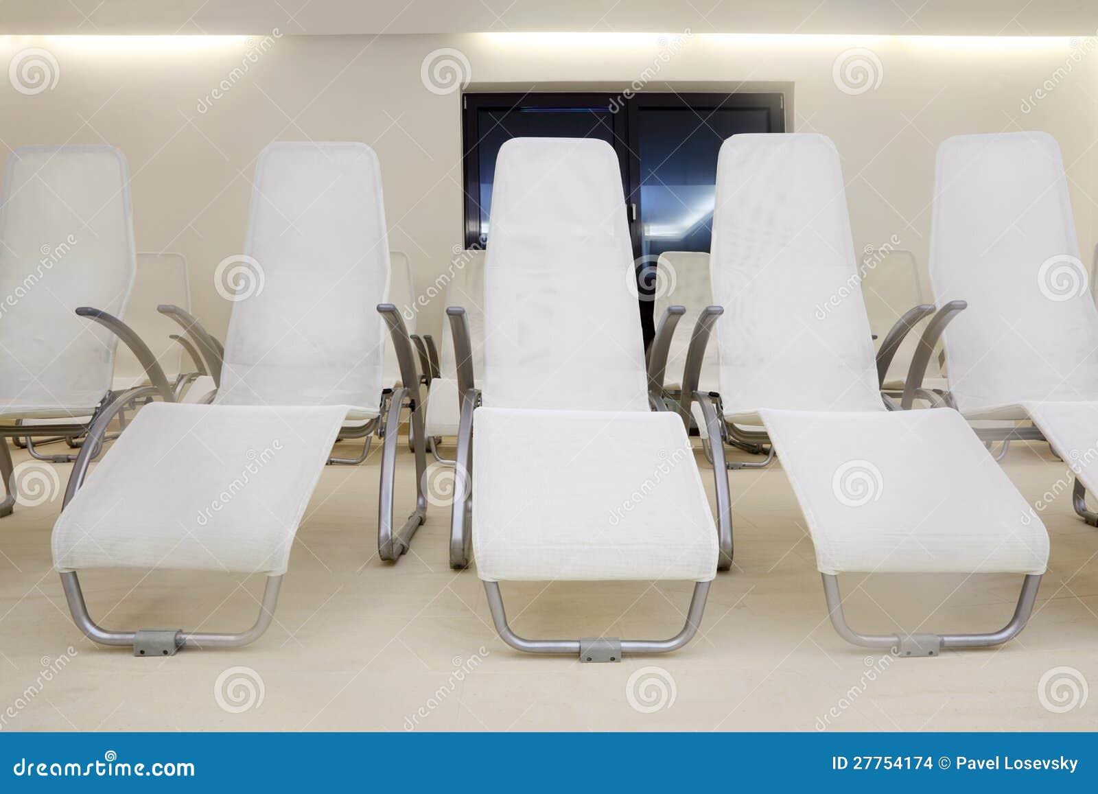 Deux lignes des sièges confortables dans la chambre vide