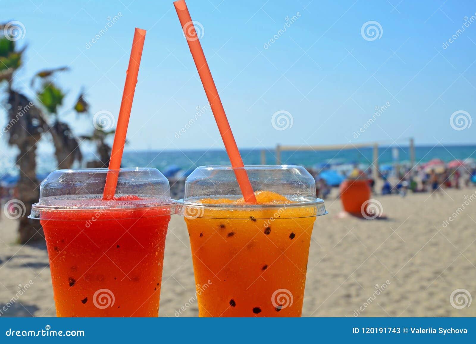 Deux macédoines de fruits lumineuses avec de la glace en verres avec des tubes Boissons fraîches sur la plage contre le contexte