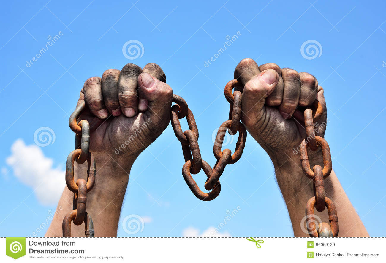 Deux mains masculines tenant une chaîne rouillée en métal