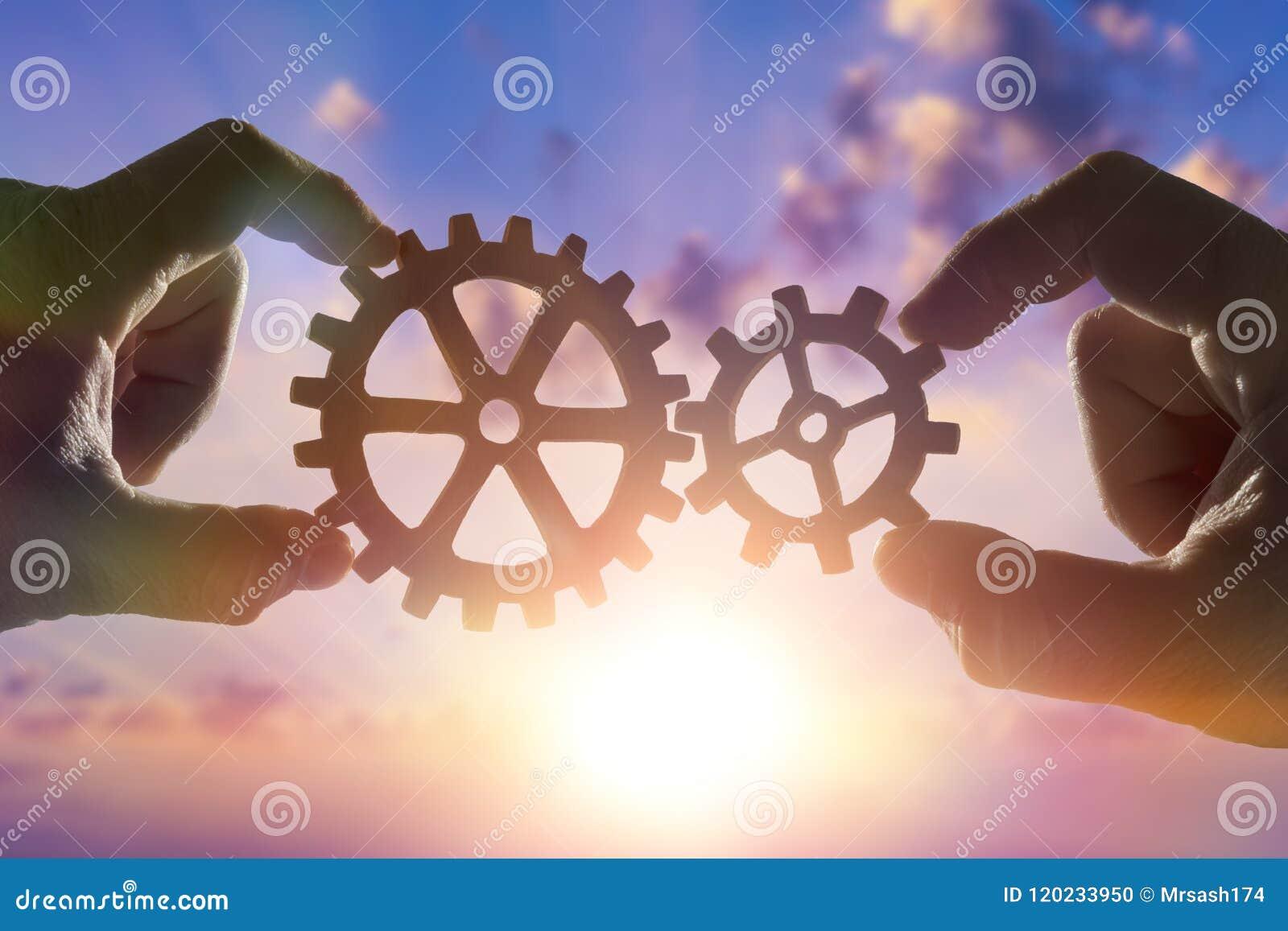 Deux mains relient les vitesses, les détails du puzzle contre le ciel avec le coucher du soleil