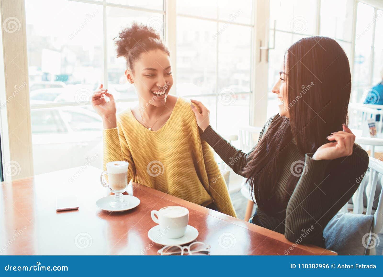 Deux meilleurs amis s asseyent en café et passent le bon temps ensemble Les filles boivent du latte et apprécier leurs