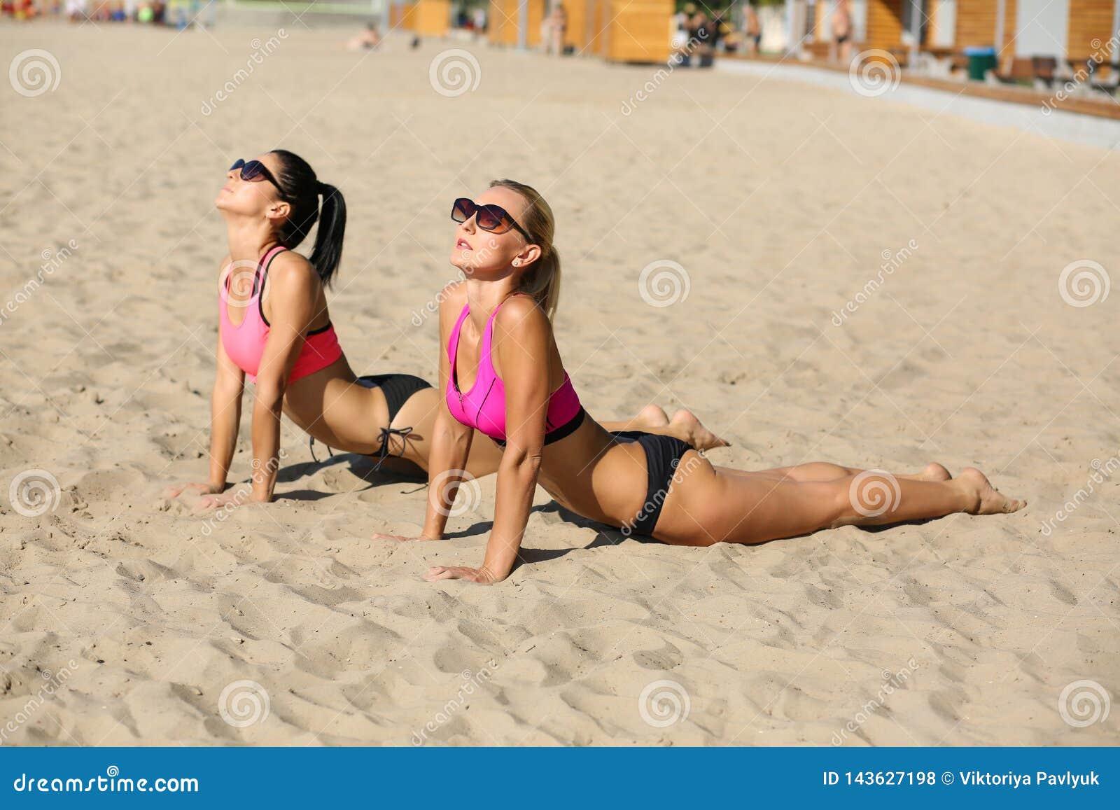 Deux modèles adorables de forme physique portant des verres et le yoga de pratique de maillot de bain ensemble à la plage