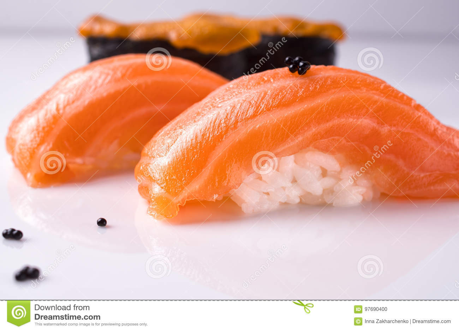 Deux morceaux de sushi saumonés japonais de nigiri, morceau uni de gunkan sur une surface réfléchie blanche ont décoré le tobiko
