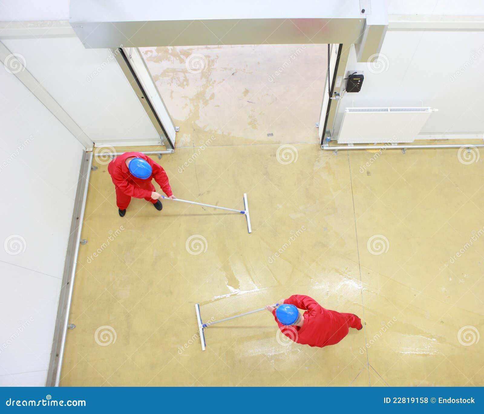 Deux ouvriers nettoyant l étage dans la construction industrielle