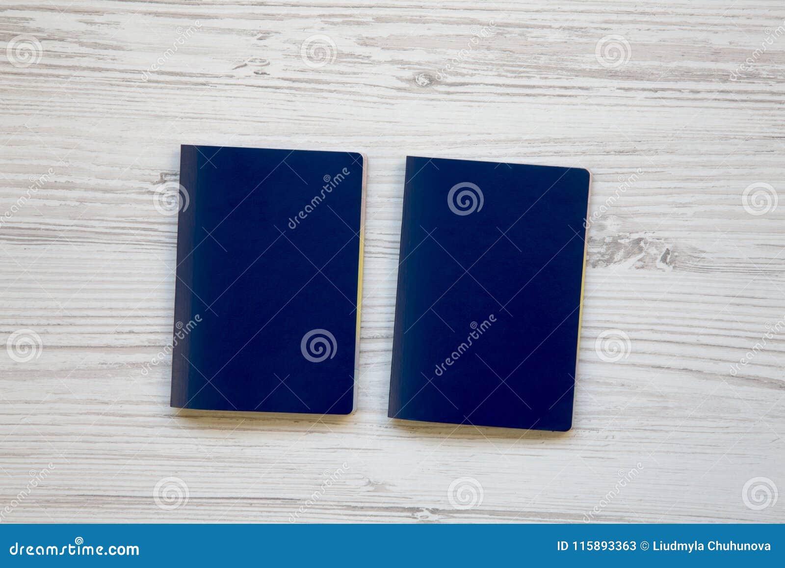 Deux passeports bleus en blanc sur en bois blanc
