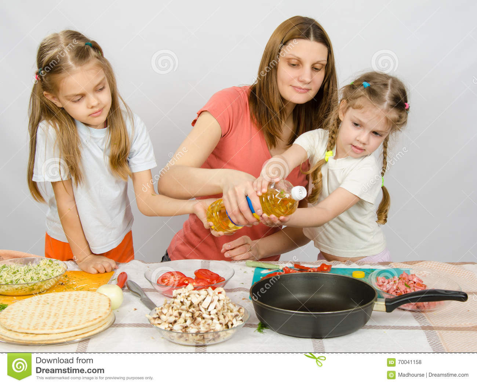 deux petites filles  u00e0 la table de cuisine avec enthousiasme pour aider ma m u00e8re  u00e0 verser l u0026 39 huile