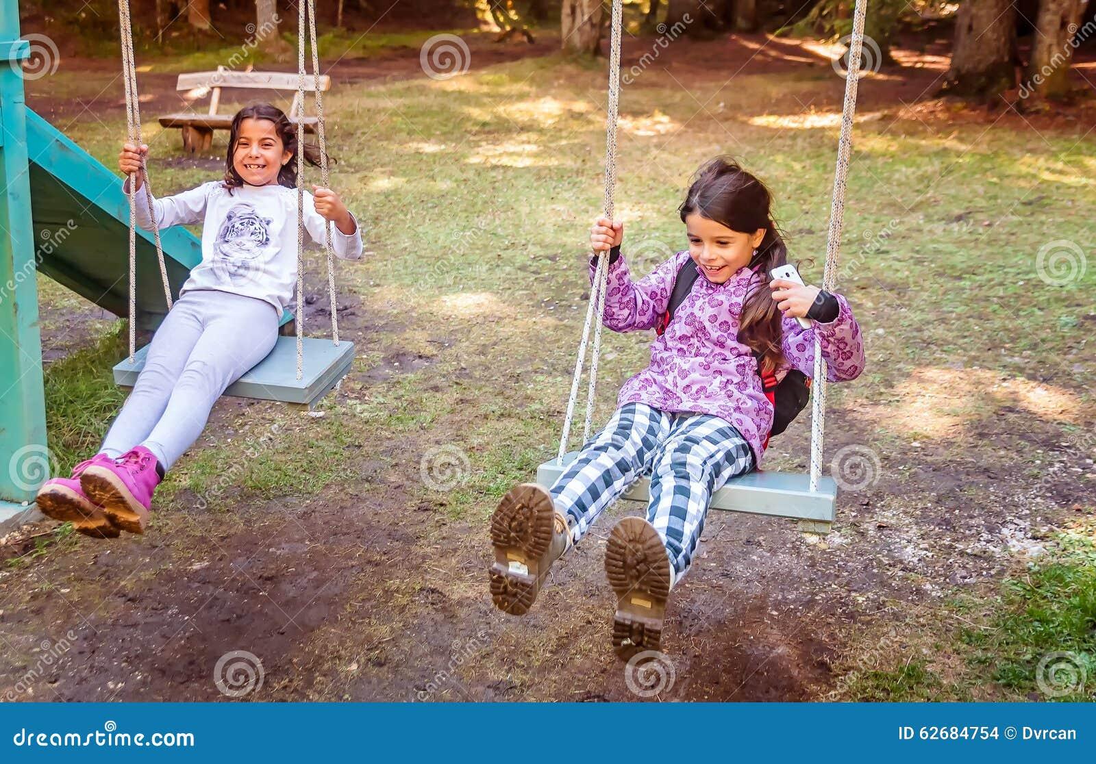 deux petites filles heureuses balan ant sur l 39 oscillation dans un terrain de jeu d 39 enfants photo. Black Bedroom Furniture Sets. Home Design Ideas