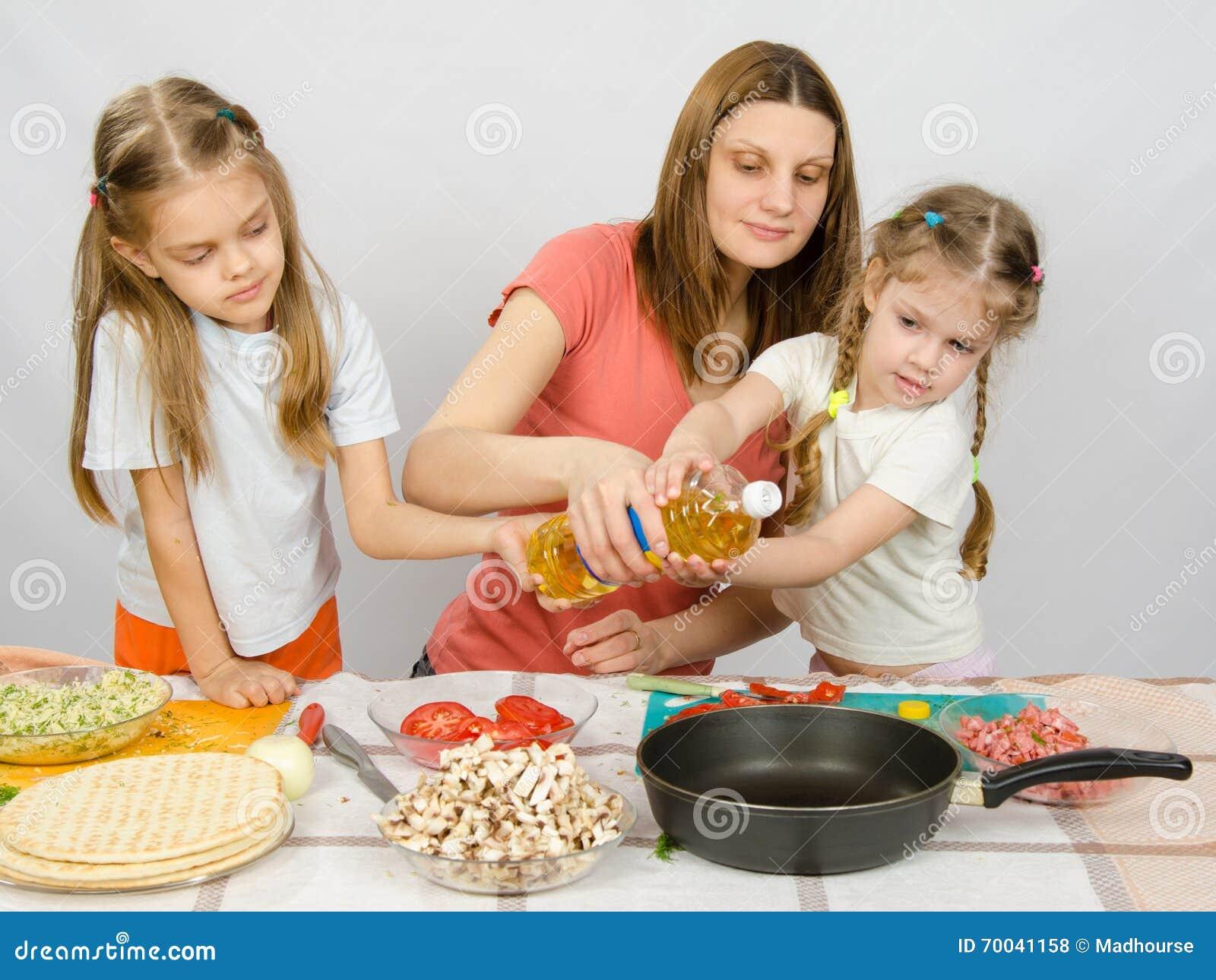 deux petites filles la table de cuisine avec enthousiasme pour aider ma m re verser l 39 huile. Black Bedroom Furniture Sets. Home Design Ideas